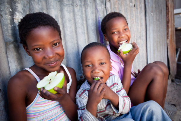 3 young African kids sitting outside eating