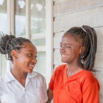 Two high school age Honduran girls from the island of Roatan have big toothy smiles on their face as they pose on a front porch. There is a washing machine on the porch. They are smiling at each other. Shot taken with Canon 5D Mark lll.
