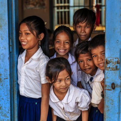 Cambodian school children standing in doorway of classroom in small village near Tonle Sap, Cambodia.